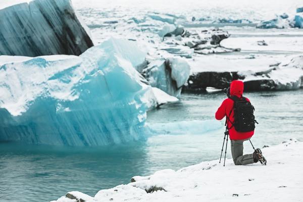 Turista tomando foto a un glaciar - Uno de los mejores planes para hacer en Islandia en invierno