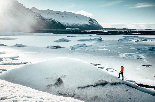 Turista caminando por montañas nevadas en Islandia - Viajar a Islandia - Guía de costes para el viajero