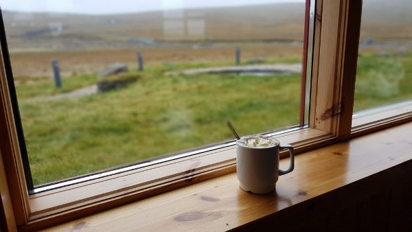 Taza de café en la venta de una estación de servicio con vistas a la naturaleza de Islandia - Diesel vs Gasolina : ¿Cuál es la mejor opción para tu viaje en Islandia?