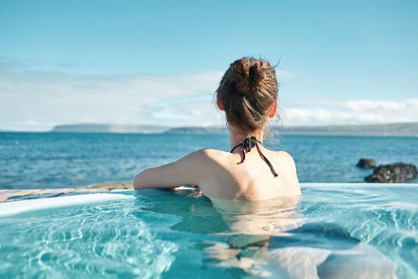 Turista contemplando el océano desde una piscina descubierta - Las mejores piscinas de Islandia en Reikiavik