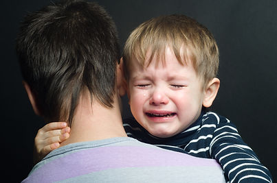 Crying child in the arms of his father.j