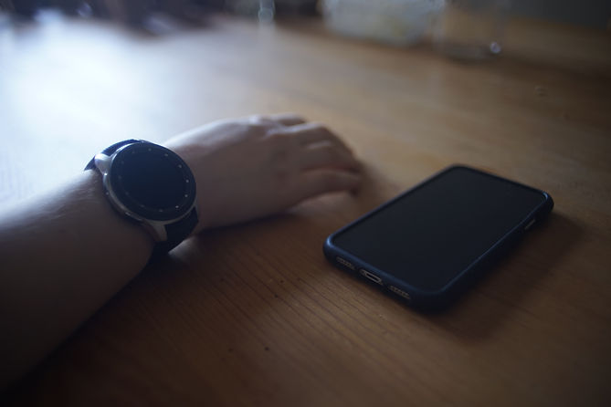 A hand with a watch on the wrist next to a phone
