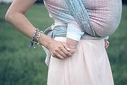 Baby im Tragetuch - Detail von Mamas Hand und Babyfuß