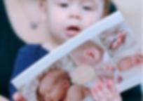 Baby hat einen Prospekt von Lichtfühler Fotografie in der Hand