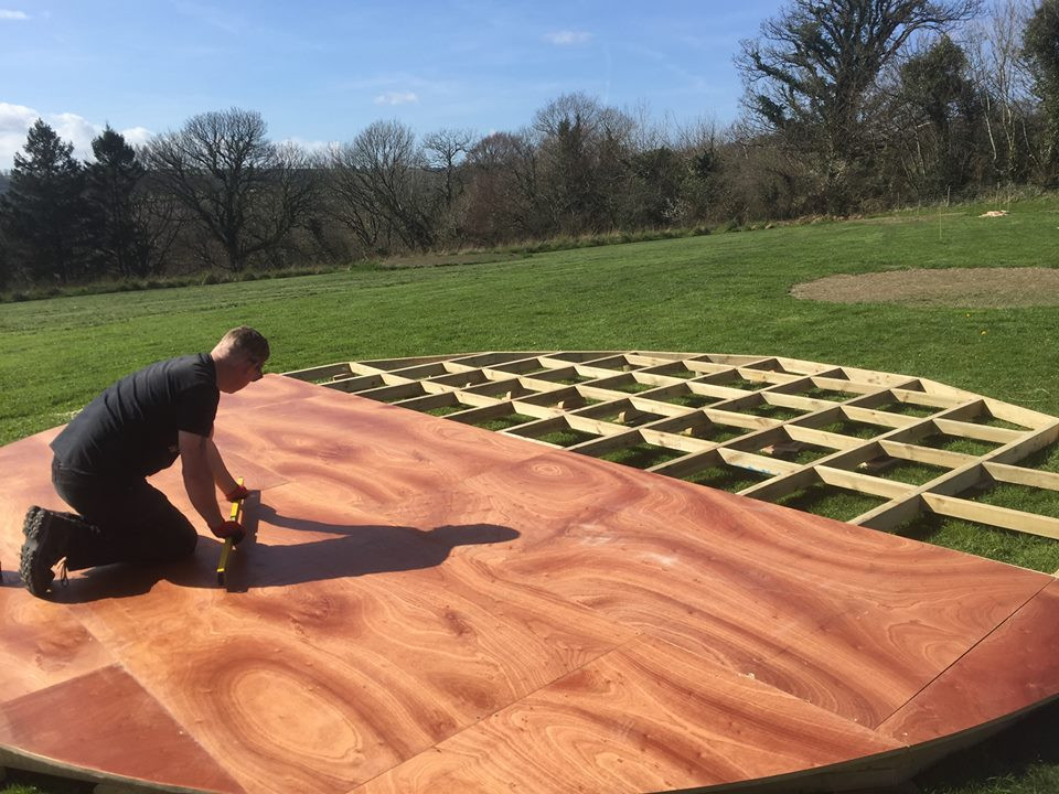 Putting the floor for Top of the Woods glamping Nature Domes down in the meadow