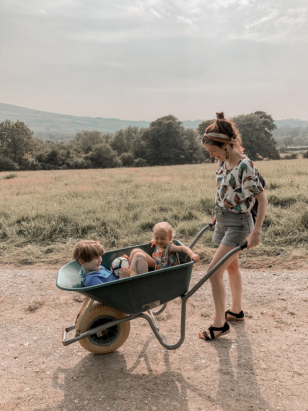 Mum pushing two children in a wheelbarrow at Top of the Woods Camping & Glamping, Pembrokeshire Wales.