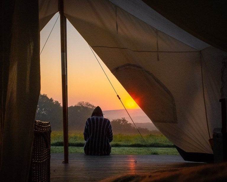 Looking out at a sunrise over the glamping Pioneer Camp meadow at Top of the Woods camping & glamping holidays Pembrokeshire Wales UK