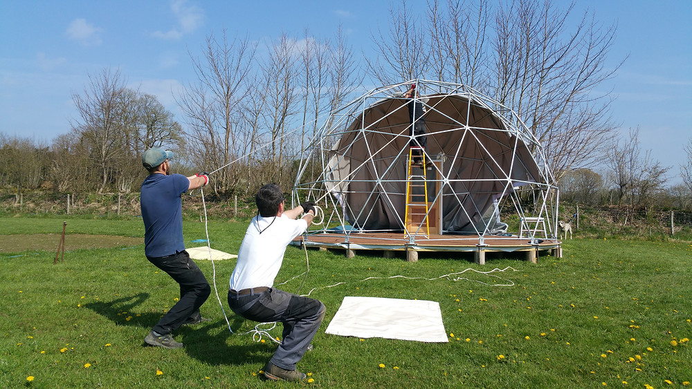 Top of the Woods glamping nature dome set up, putting the canvas on