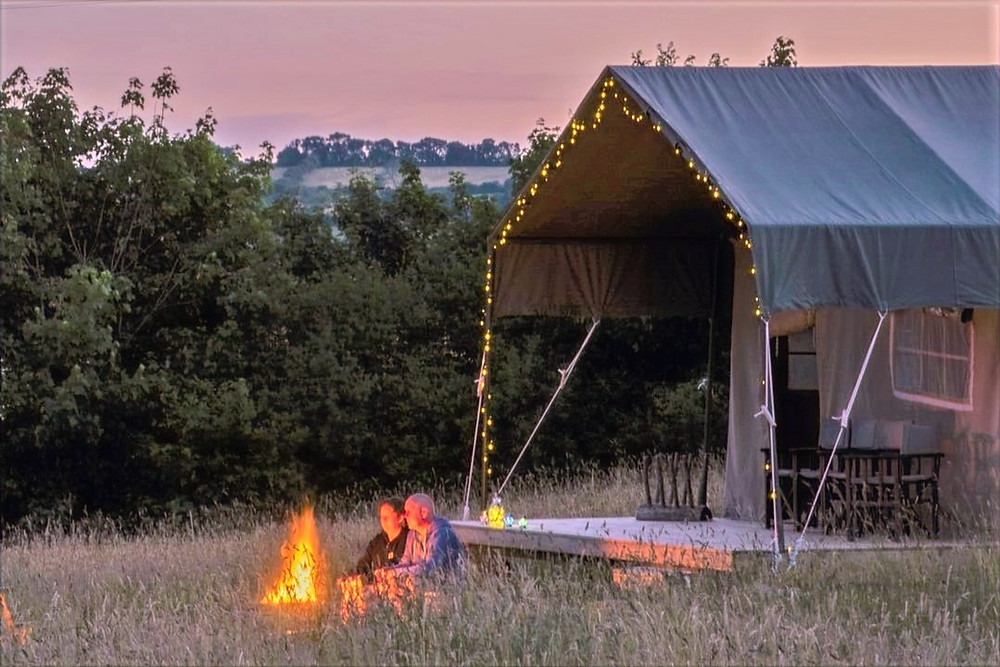 Glamping Safari Lodge and couple sat by the campfire at Top of the Woods eco camping & glamping Pembrokeshire Wales UK