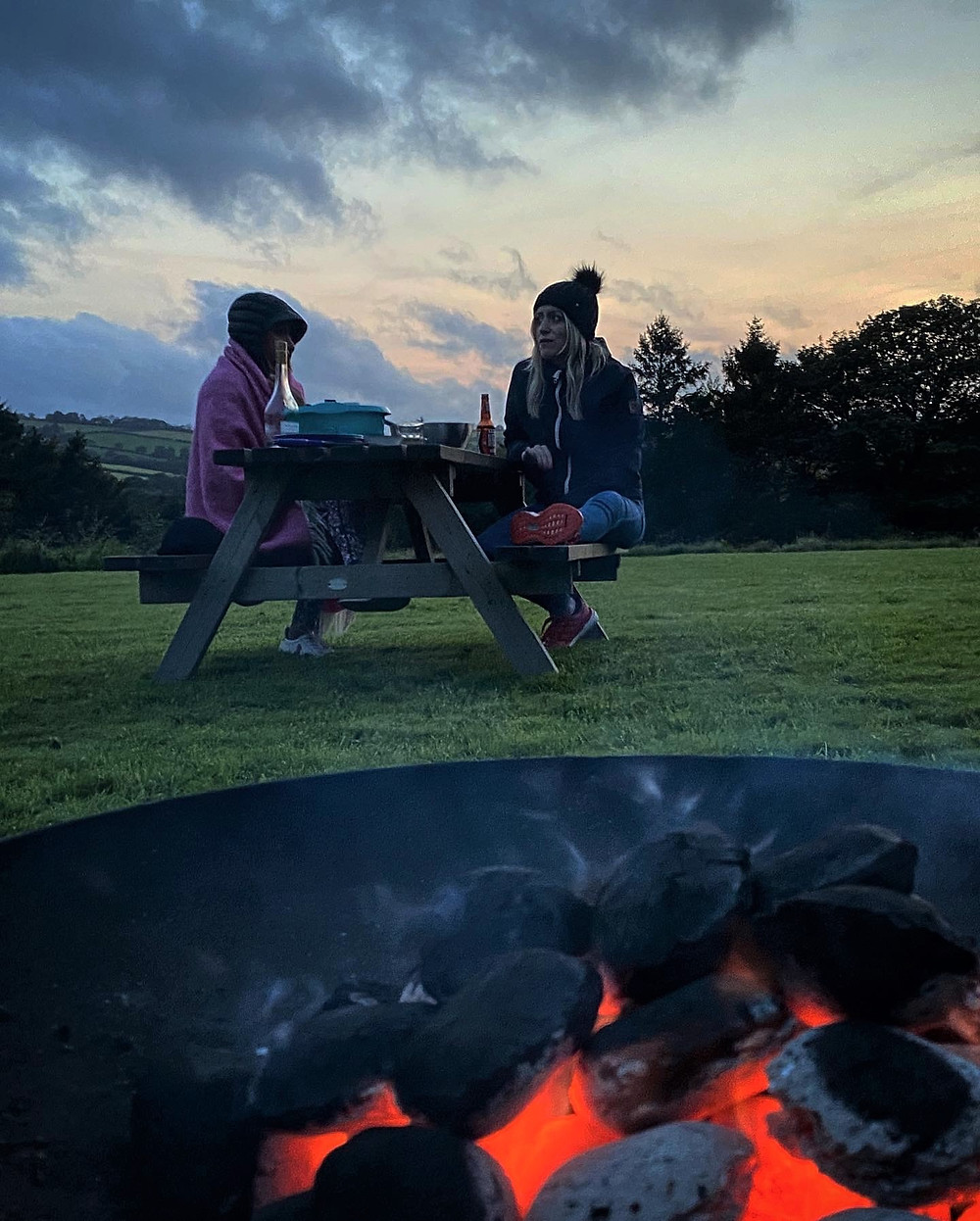 Friends sitting in front of a campfire at Top of the Woods Camping & Glamping, Pembrokeshire Wales.