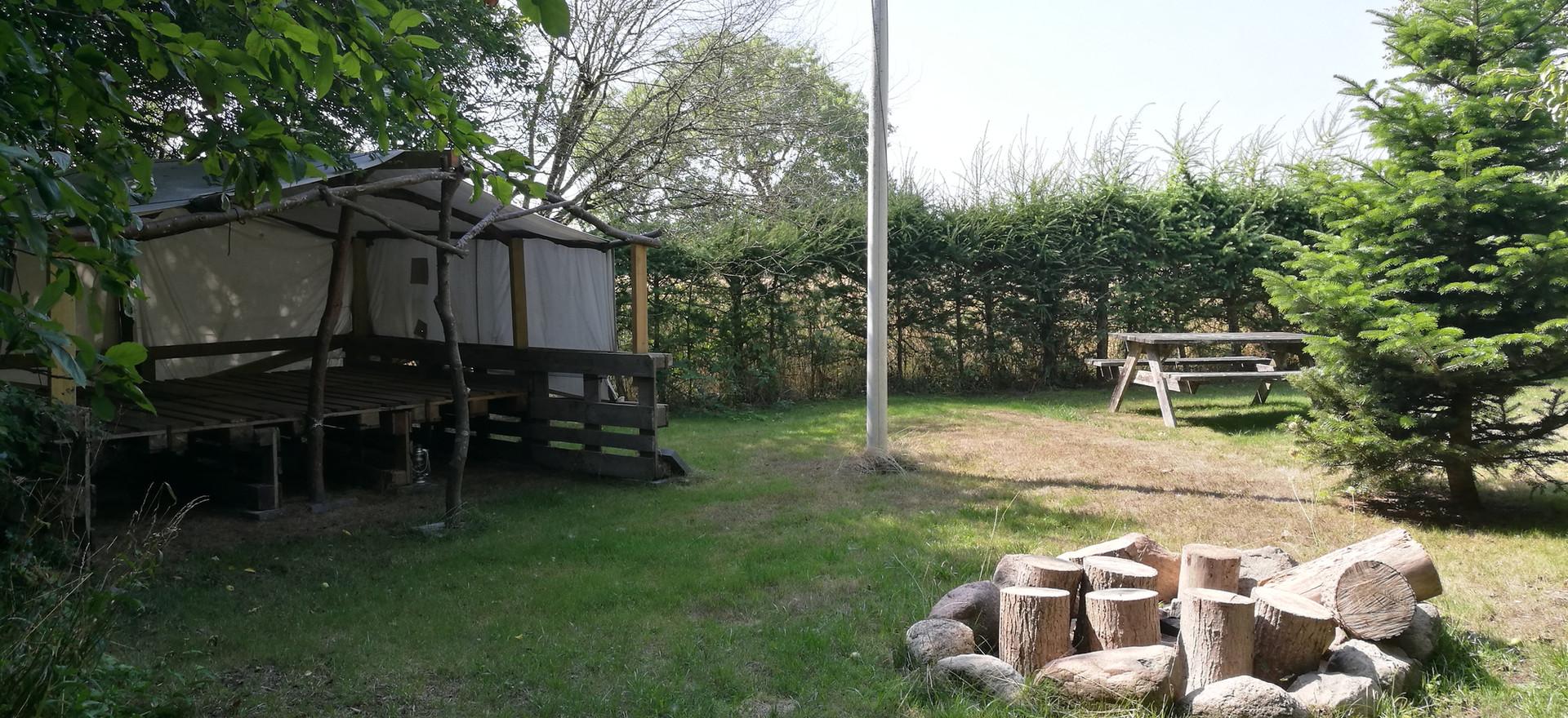 Shelter og bålplads med siddestubbe.
