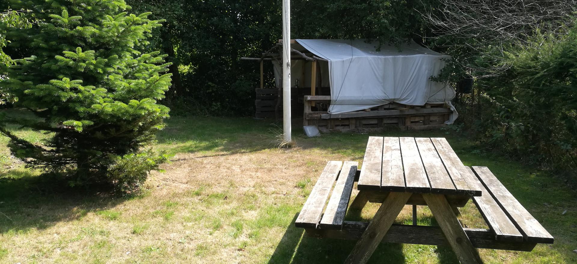 Der er bordbænk sæt og en primitiv shelter i haven.