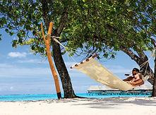 Honeymoon couple lying on a hammock at the Sofitel Moorea Beach Resort