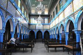 Inside view of the synagogue featuring long wooden benches and soaring blue arches