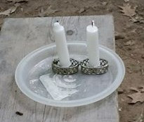 Candles in travelling holders on a picnic table