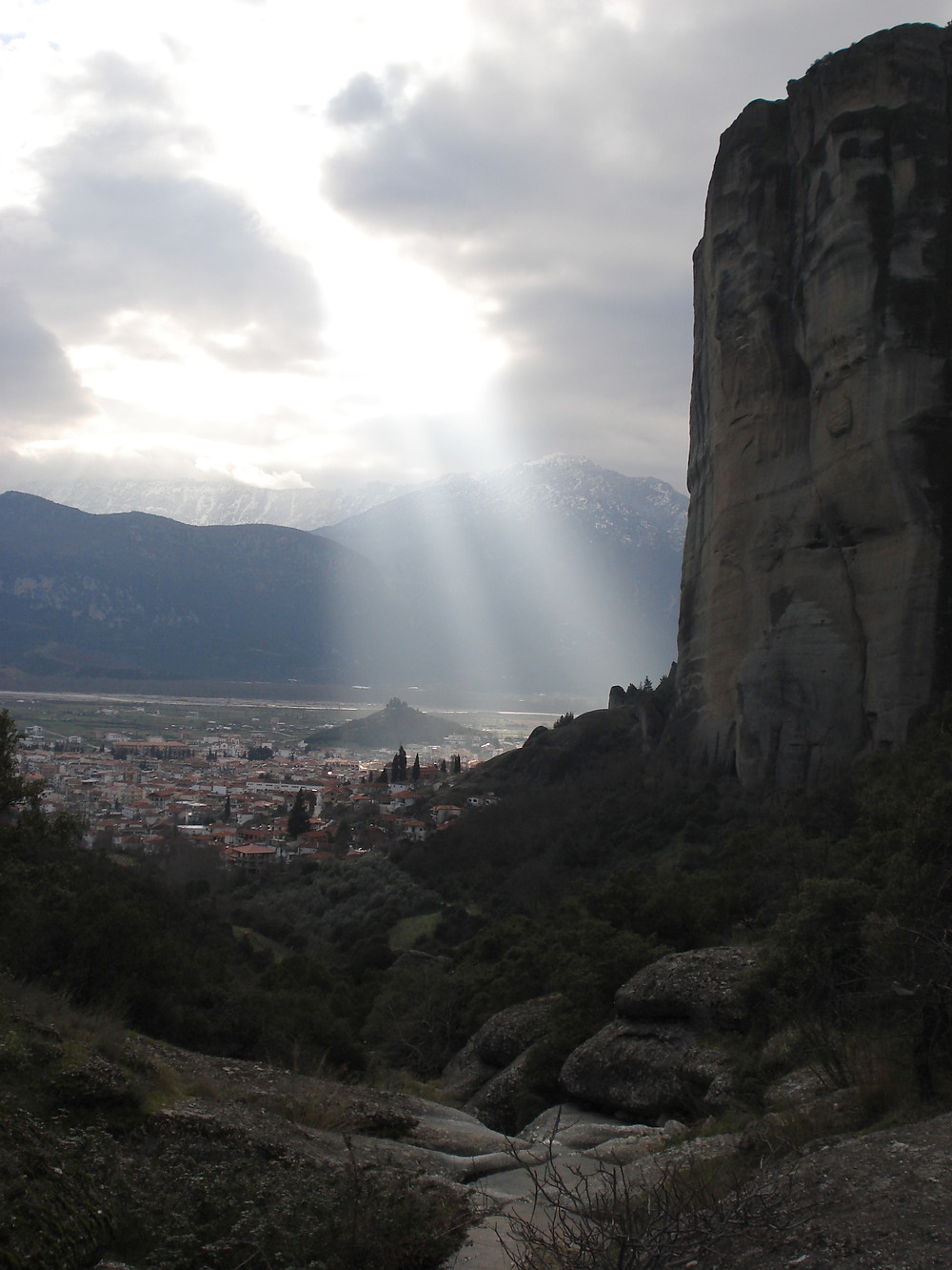 A cliff in the desert, sunshine breaking through clouds.