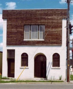 White and wood two-storey building, arched windows and doors - Sons of Jacob synagogue
