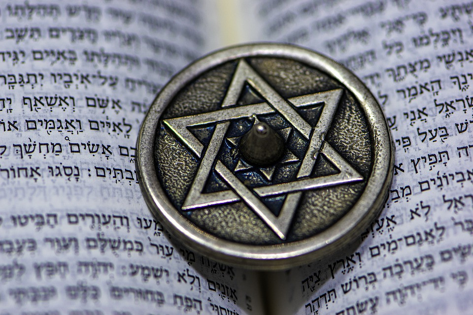 A star of David on a metal circle atop an open page of Hebrew text