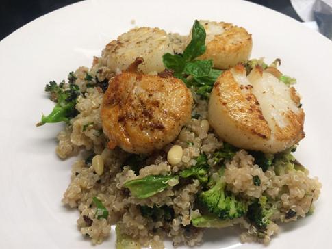 Seared scallop on top of quinoa brocoli salad