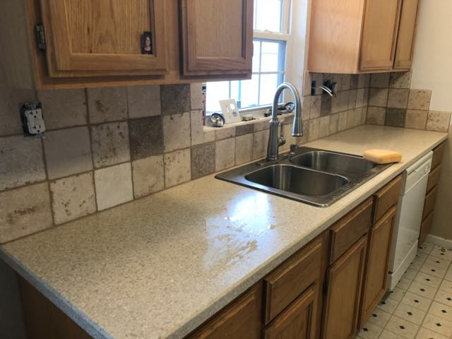 Solid surface countertop and full height tumbled marble backsplash