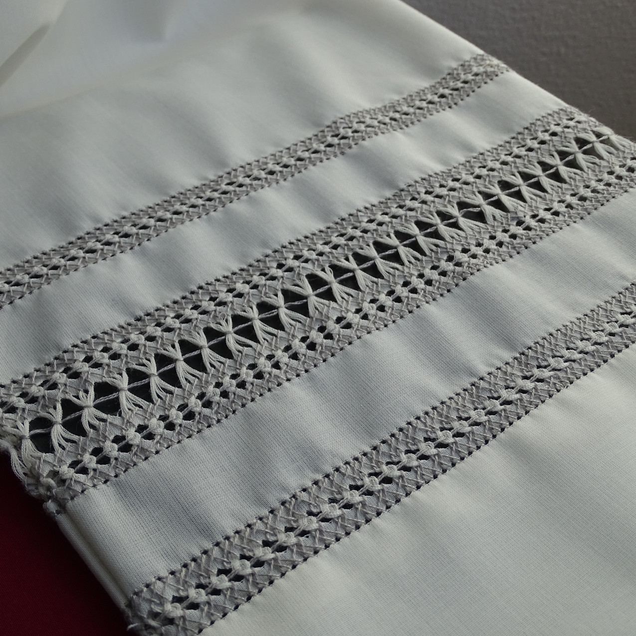 Sfilatura di gigliuccio a mano realizzata sulla manica di un camice sacerdotale in fresco di lana
