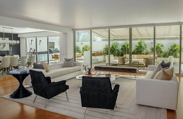 Contemporary living room. Large neutral sofa's, expansive windows, black lounge chairs, large dining table and white chairs, neutral engraved area rug, black leather bench, open airy space, Santa Monica, CA