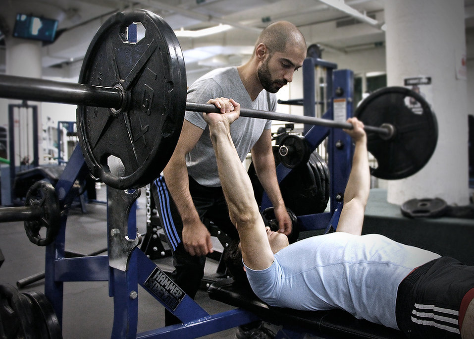 Personal trainer spotting a barbell bench press for his client