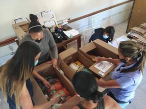 Personas organizando alimentos para ser entregado a personas con discapacidad