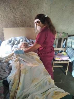 Adulto mayor en cama recibiendo terapia de rehabilitación