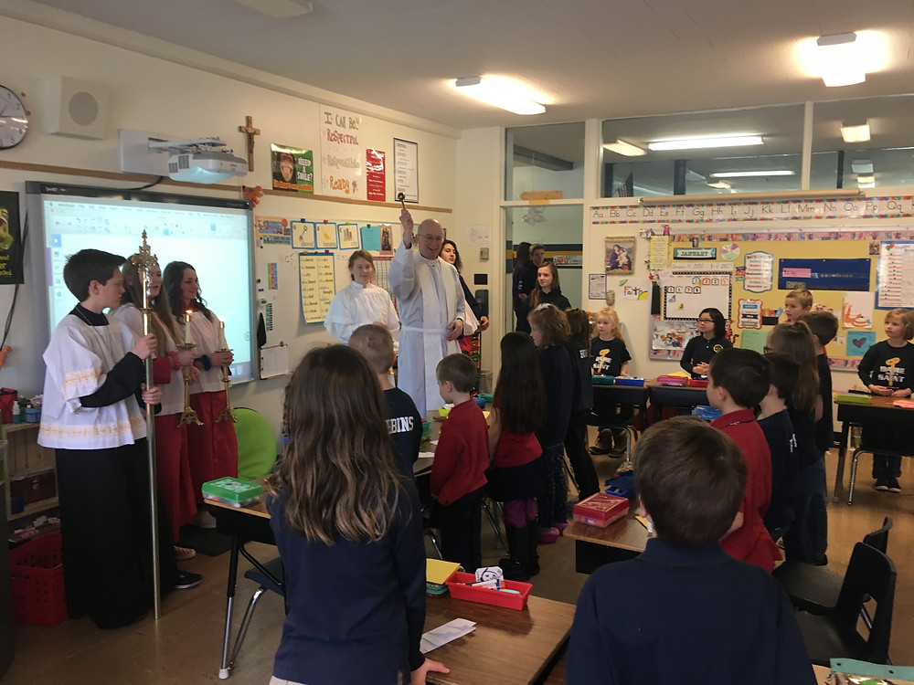 Father Rod blessing 2nd grade classroom