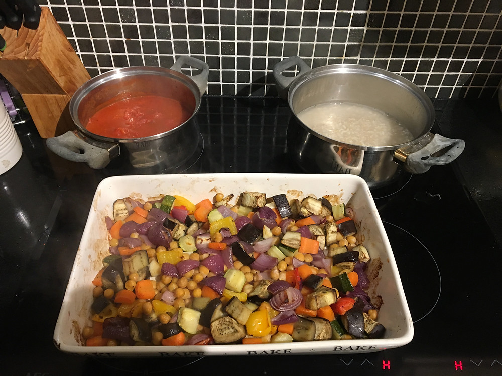 Tray of roasted vegetables, pan of tomato sauce and pan of brown rice