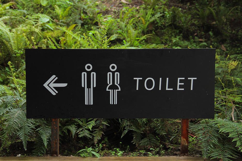 Kuvassa on musta WC-kyltti, jossa valkoisella nuoli vasemmalle, miesten ja naisten kuvat ja sana toilet. Taustalla on vihreää kasvillisuutta.