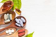 Variety of vitamin pills in wooden spoon