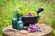 black mortar with healing herbs and sage