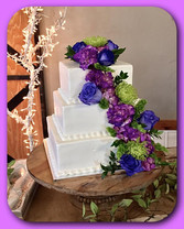 Square tiered wedding cake with fresh flowers