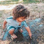 boy playing outside mud