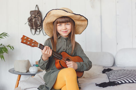 kid-girl-in-hat-playing-ukulele-at-home-