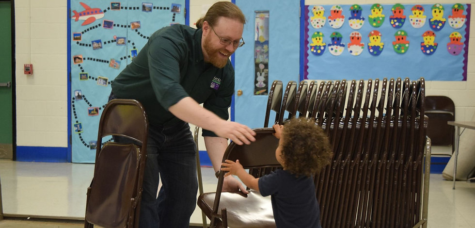 A young volunteer helps an adult set up