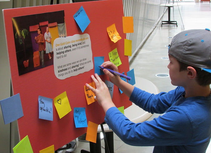 Young audience member writes on activity board