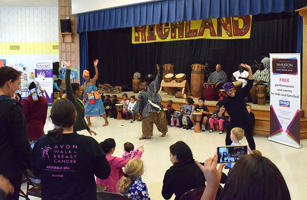 Kids from the audience play drums for dancers at Wheaton Family Theatre Series event