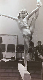 Old photograph of a gymnast girl standing on one foot on a beam