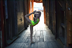 Flexible Norwegian baton twirler posing at Bryggen in Bergen, Norway wearing her costume. Sportsdrill.