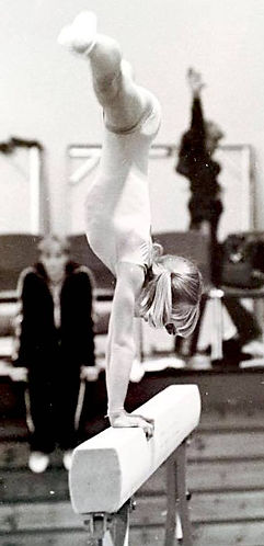Old photograph of a gymnast girl doing a cartwheel on a beam