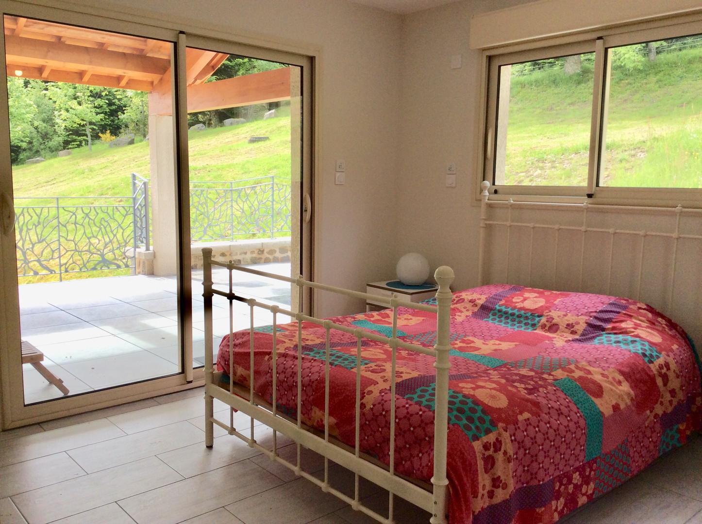 La chambre du rez de chaussée et son accès à la terrasse