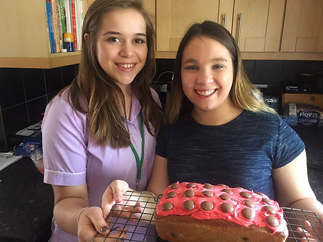 Carer standing next to young adult client, who has baked a sponge cake with chocolate buttons