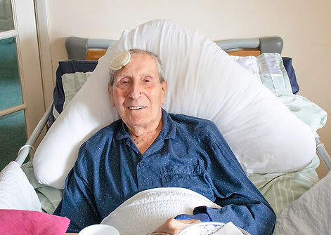End of life client, smiling from is bed