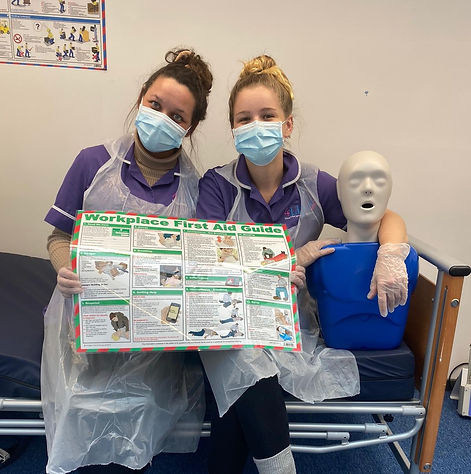 Two healthcare workers holding up a 'Workplace First Aid' poster and clutching a First Aid mannequin