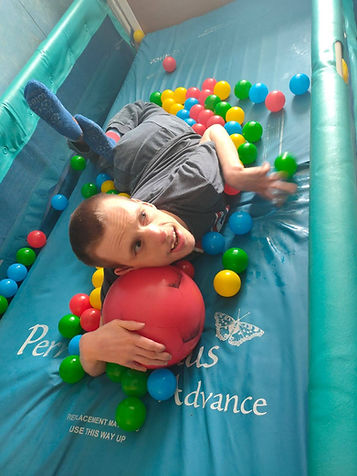 Young adult with complex needs, playing in an indoor soft play centre