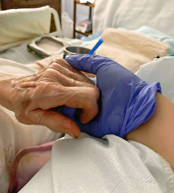 Carer holding the hand of an elderly client