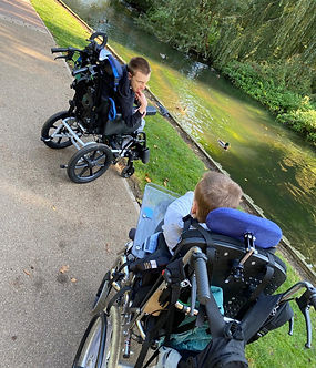 Two brothers in wheelchairs by the river